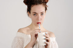 Lovely young girl is drinking with a straw. studio shot with light background. Stock Photo