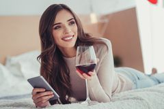 Lovely young girl enjoying red wine at home stock photo