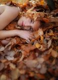 Lovely young girl is lying on autumn leaves, covered with colored autumnal leaves, with free space for your text. royalty free stock photo