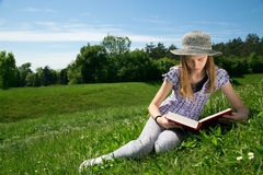 Lovely Young Girl Reading A Book While Sitting In A Beautiful Field Of Grass Stock Photography