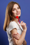 Lovely young girl with red heart shaped lollipop Stock Image