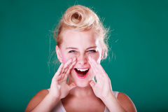 Lovely young girl screaming, hands close to mouth. Yelling gestures concept. Lovely pin up girl screaming with hands close to mouth. Studio shot on green Royalty Free Stock Photos