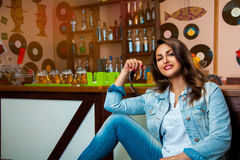 Lovely young girl smiling on camera and sit at bar stock photography