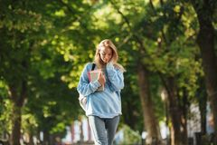 Lovely young girl student with backpack carrying books. Walking at the park Royalty Free Stock Image