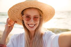 Lovely young girl in summer hat. And swimwear spending time at the beach, taking a selfie Royalty Free Stock Images