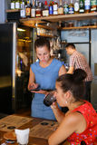 Lovely young girl waiter holds tablet and takes order communicat Royalty Free Stock Photography