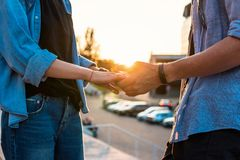 Lovely young hipster couple dating during summer sunset. Closeup view of hands of lovely young couple dating during summer sunset. they wear jeans clothes stock photo
