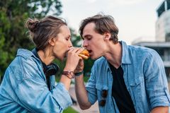 Lovely young hipster couple dating during summer sunset. They wear jeans clothes. they eat burger fastfood together royalty free stock images