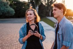 Lovely young hipster couple dating during summer sunset. They wear jeans clothes. modern youth relationship stock images