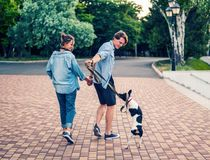 Lovely young hipster couple dating during summer sunset. Lovely young hipster couple walking with dog during summer sunset. they wear jeans clothes. modern stock images