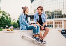 Lovely young hipster couple dating during summer sunset. They wear jeans clothes. they eat and drink royalty free stock images