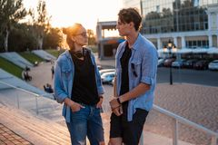 Lovely young hipster couple dating during summer sunset. They wear jeans clothes. modern youth relationship royalty free stock images