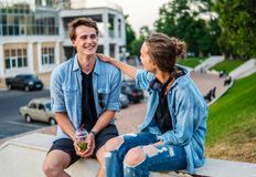 Lovely young hipster couple dating during summer sunset. They wear jeans clothes. modern youth relationship royalty free stock image