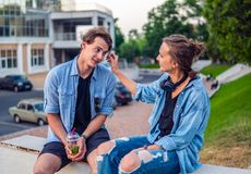 Lovely young hipster couple dating during summer sunset. They wear jeans clothes. modern youth relationship stock image