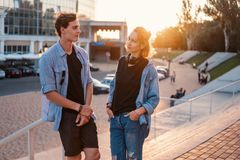Lovely young hipster couple dating during summer sunset. They wear jeans clothes. modern youth relationship stock photography