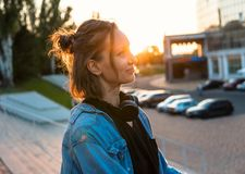 Lovely young hipster girl standing during summer sunset. She has headphones royalty free stock photos