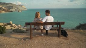 Young hugging couple is sitting on a bench on a cliff with a gorgeous picturesque view of the endless sea with clear. Lovely young hugging couple is sitting on a stock video