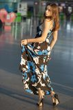 Lovely young lady. Posing at the airport dressed in a long dress stock image