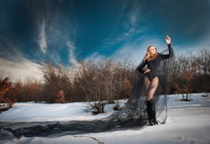 Lovely young lady posing dramatically with long black veil in winter scenery. Blonde woman with cloudy sky in background - outdoor Stock Image