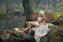 Lovely young lady sitting near river in enchanted woods. Sensual blonde with white clothes posing provocatively in autumnal park. Royalty Free Stock Photos