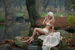 Lovely young lady sitting near river in enchanted woods. Sensual blonde with white clothes posing provocatively in autumnal park. Girl with fairy look in fall Royalty Free Stock Images