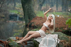 Lovely young lady sitting near river in enchanted woods. Sensual blonde with white clothes posing provocatively in autumnal park. Girl with fairy look in fall Stock Photo