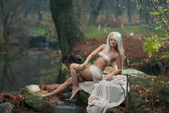 Lovely young lady sitting near river in enchanted woods. Sensual blonde with white clothes posing provocatively in autumnal park. Girl with fairy look in fall Stock Photos