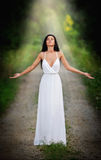 Lovely young lady wearing an elegant long white dress enjoying the beams of celestial light on her face in enchanted woods. Long h Stock Photos