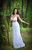 Lovely young lady wearing an elegant long white dress enjoying the beams of celestial light on her face in enchanted woods. Long h Royalty Free Stock Photo