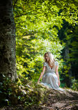Lovely young lady wearing elegant white dress enjoying the beams of celestial light on her face in enchanted woods. Pretty blonde Stock Photos