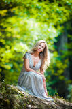 Lovely young lady wearing elegant white dress enjoying the beams of celestial light on her face in enchanted woods. Pretty blonde Royalty Free Stock Photo