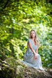 Lovely young lady wearing elegant white dress enjoying the beams of celestial light on her face in enchanted woods. Pretty blonde Stock Photo