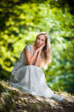 Lovely young lady wearing elegant white dress enjoying the beams of celestial light on her face in enchanted woods. Pretty blonde Stock Images
