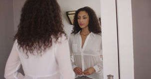 Lovely young latino woman dressing in front of mirror Stock Images