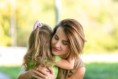 Lovely young mom and daughter in warm sunny summer day. Happy family mother and child little daughter hugging and stock photos