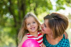 Lovely young mom and daughter in warm sunny summer day. Happy family mother and child little daughter playing and. Walking in the Park and enjoying the Stock Photo
