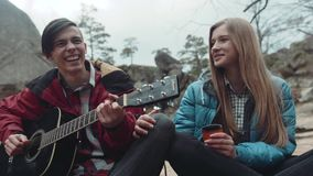 Lovely young people singing together a song, happily laughing during the picnic in the autumn park. Happy memories. Romance, love. Cloudy weather, strong wind stock video footage