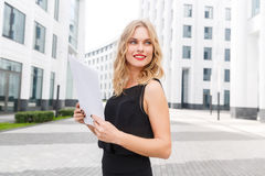 Lovely young stylish lady in black blouse and with papers Stock Image