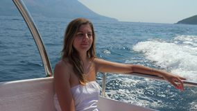 Young Pretty Woman Sitting In Boat And Sailing On The Sea Slow Motion. 4K. Lovely young tanned brunette woman floating on a boat on the sea. She sits in the stock video footage