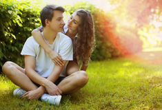 Lovely young teen couple in love having fun on lawn in park. In summer sunny day stock photography