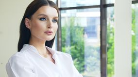 Lovely young woman with beautiful blue eyes thought standing while standing at the office window stock footage