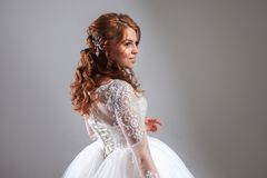 Lovely young woman bride in lavish wedding dress. Light background. Stock Images