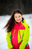 Lovely young woman brunette in a bright jacket on walk in winter day. Royalty Free Stock Photography