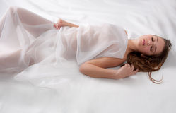 Lovely Young Woman Covered in Sheer White Sheet Royalty Free Stock Photography