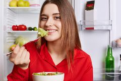 Lovely young woman eats fresh vegetable salad, tastes cabbage on fork, poses against opened refrigerator full of fruits and vegeta. Bles, has positive expression Royalty Free Stock Photos