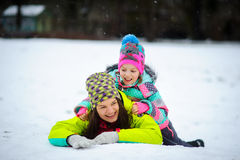 Lovely young woman and girl in bright jackets lie on snow. Royalty Free Stock Photography