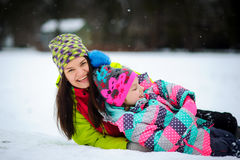 Lovely young woman and girl in bright jackets lie on snow. Stock Photo
