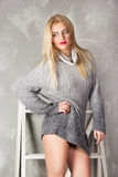 Lovely young woman in a gray pullover against a background of plaster and flax. Sexy blonde with beautiful eyes in a sweater on a gray background Royalty Free Stock Photography