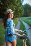 Lovely young woman in a hat with a bicycle in a park Royalty Free Stock Photo