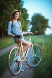Lovely young woman in a hat with a bicycle in a park Royalty Free Stock Image